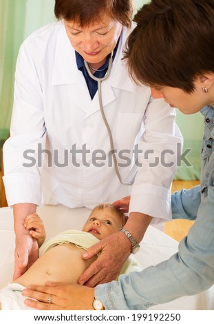 mature  doctor examing baby  at clinic   - stock photo