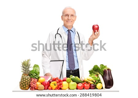 Mature doctor holding an apple and standing behind a table full of fruits and vegetables isolated on white background - stock photo