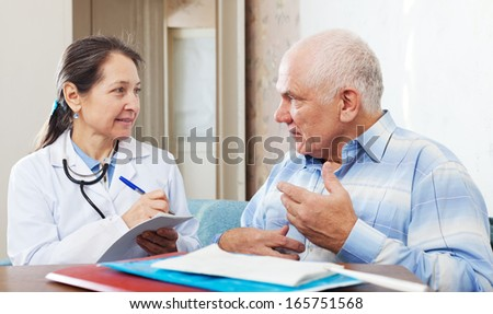 Mature doctor of prescribes to senior patient the medication - stock photo