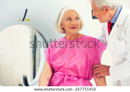 Mature doctor reassuring female patient about undergoing scan. - stock photo