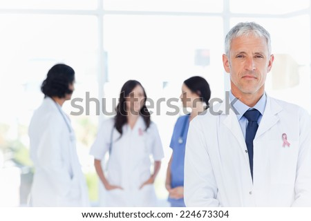 Mature doctor standing in the foreground wearing breast cancer awareness ribbon - stock photo