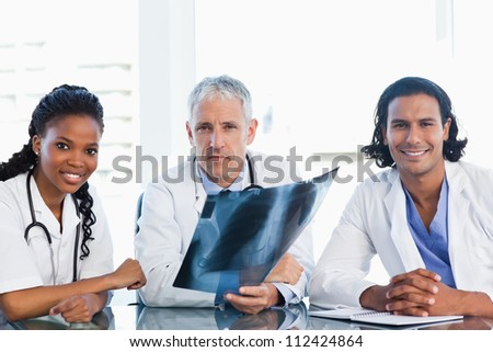 Mature doctor with smiling colleagues looking at an x-ray scan of lungs - stock photo