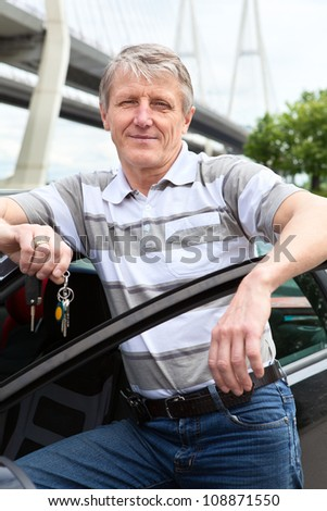 Mature driver with ignition key standing near the car - stock photo