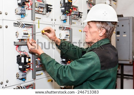 Mature electrician working in white hard hat with cables and wires. Russian people in Russia. Screwdriver in hand