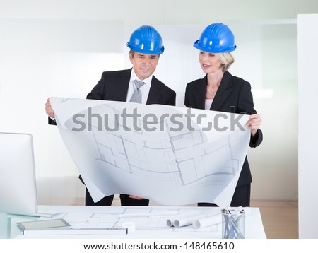 Mature Engineers Looking At Blueprint Wearing Hardhat In Office - stock photo