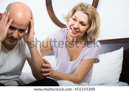 Mature european  wife warmly comforting upset husband in bedroom