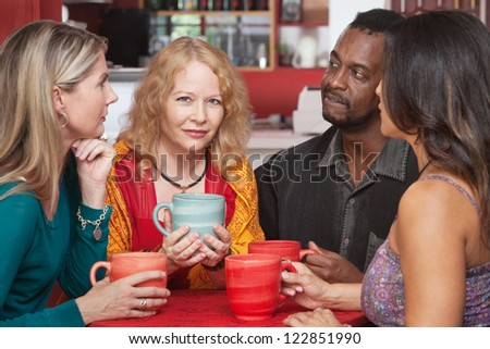 Mature European woman with sympathetic friends in coffeehouse - stock photo