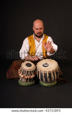 Mature exotic arabic darabuka drummer with two drums. percussion. black background - stock photo