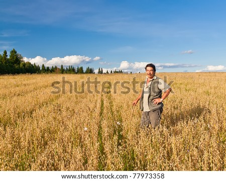 Mature farmer looking with satisfaction at his cultivated field and having care of wheat - stock photo