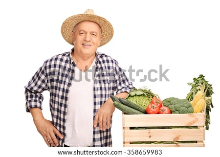 Mature farmer posing next to a wooden crate full of fresh vegetables isolated on white background