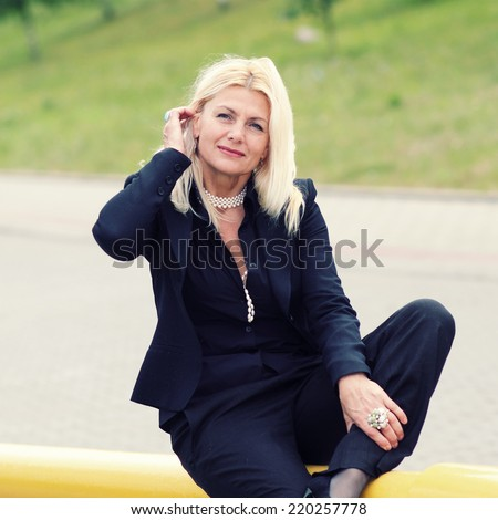 mature fashionable woman in black suit - stock photo