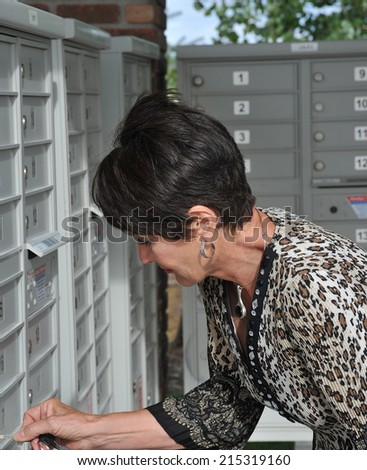 Mature female beauty getting mail out of her mailbox outside. - stock photo