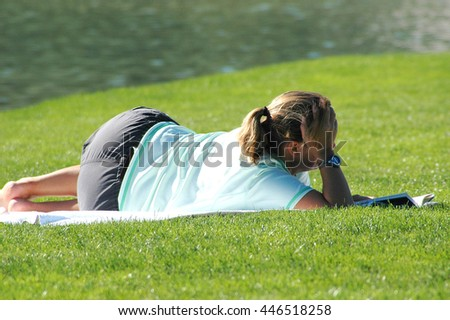 Mature female blond beauty relaxing in a park outdoors.