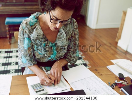 Mature female bookkeeper  busy crunching numbers on her calculator, while wearing glasses and working from her home office at her wooden desk - stock photo