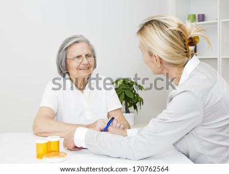 Mature female caregiver visit her senior woman patient at home. - stock photo