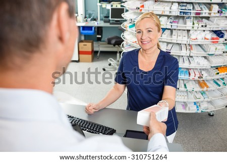 Mature female chemist smiling while giving medicine to male customer in pharmacy