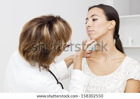 Mature female doctor examining her young female  patient. - stock photo