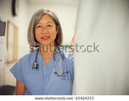 Mature female doctor posing - stock photo