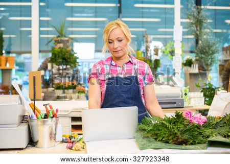 Mature female florist using laptop at counter in flower shop - stock photo