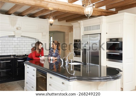 Mature Female Friends Standing In New Luxury Fitted Kitchen And Talking - stock photo
