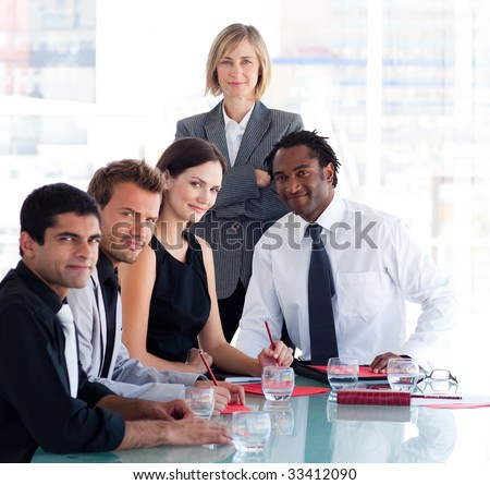 Mature female manager with her team looking at the camera - stock photo