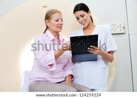 Mature female patient having discussion with nurse holding clipboard