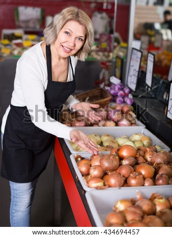 Mature female posing with ordinary vegetables in market