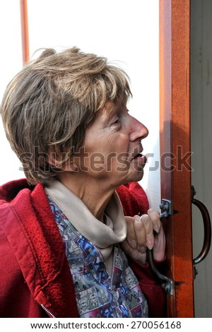 Mature female ranch er looking in at her horses in the stable. - stock photo