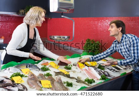 Mature female seller and male customer choosing chilled fish at market