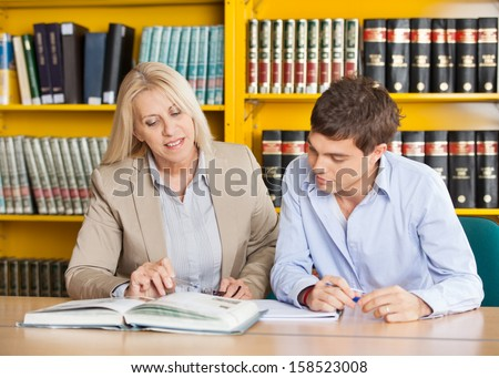 Mature female teacher explaining student while sitting at table in university library - stock photo
