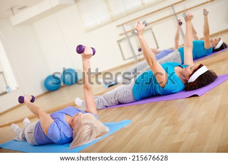 Mature females doing exercise with barbells in sport club - stock photo