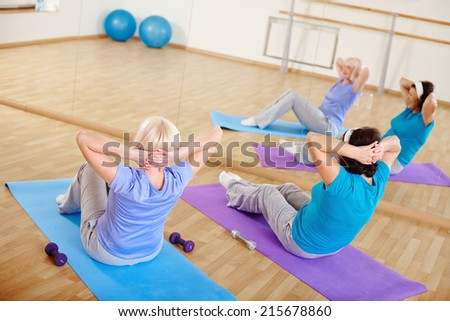 Mature females doing sit-ups on mats in sport gym  - stock photo