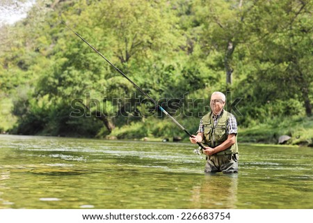 Mature fisherman fishing in a river on a sunny day - stock photo