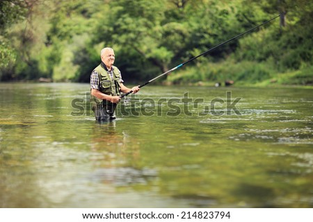 Mature fisherman fishing in a river with a fishing rod - stock photo