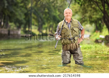 Mature fisherman posing with fishing rod in river, outdoors - stock photo