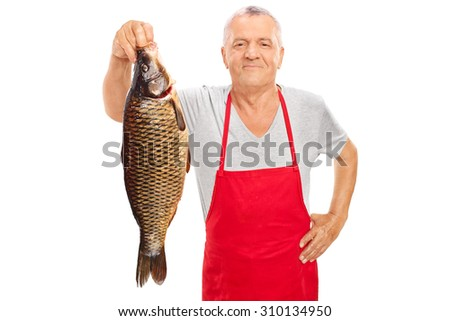 Mature fishmonger in a red apron holding a large freshwater fish and looking at the camera isolated on white background - stock photo