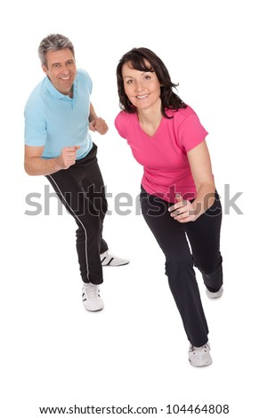 Mature fitness couple running towards camera. Isolated on white