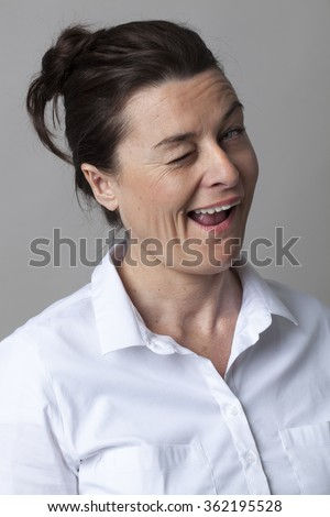 mature flirting concept - pretty 40s woman winking for fun and seduction with serenity, studio shot - stock photo