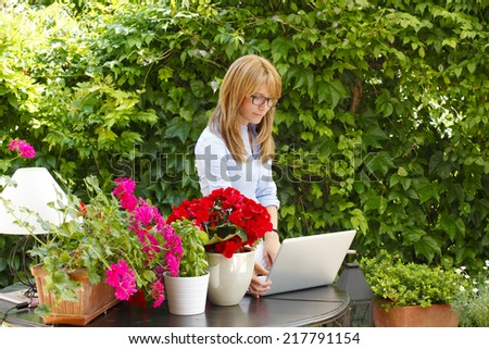 Mature florist working on laptop in flower shop.  Small business.  - stock photo