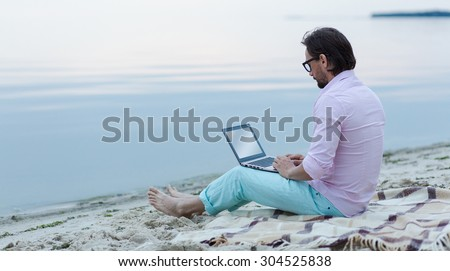 Mature freelancer working on laptop. Author in glasses writing poem at the beach. He is becoming inspired by the beautiful sea. - stock photo