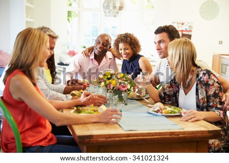 Mature Friends Sitting Around Table At Dinner Party - stock photo