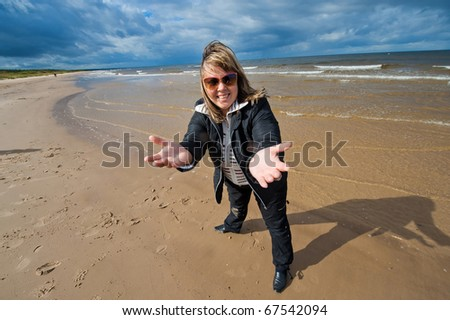 Mature funny attractive woman in sunglasses relaxing at the Baltic sea in autumn day.