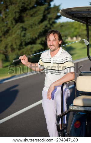 Mature golf player smilling near white gold car. Man in T-shirt and sports trousers keeping brassie in his right hand.