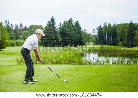 Mature Golfer on a Golf Course (ready to swing) - stock photo