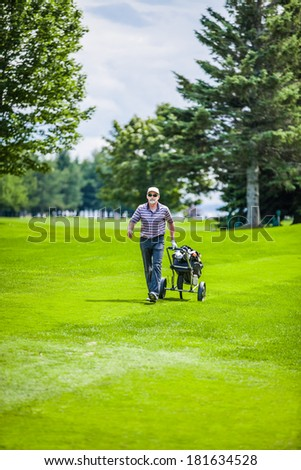Mature Golfer on a Golf Course Walking with Golf bag