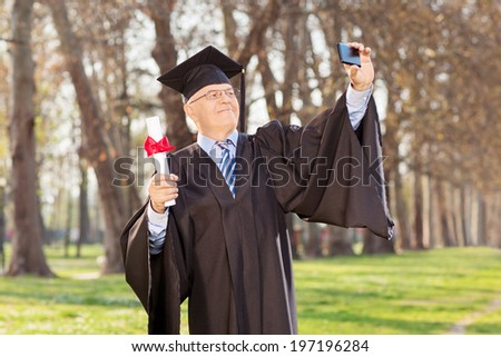 Mature graduate taking selfie in park with diploma in hand - stock photo