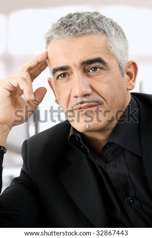 Mature gray haired creative looking businessman thinking.