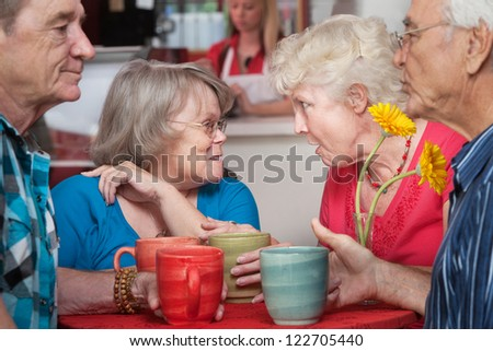 Mature group of husbands and wives gossiping in a restaurant - stock photo