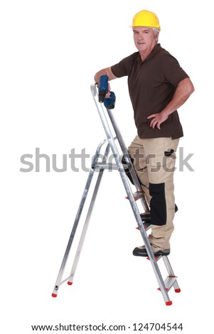 Mature handyman with drill climbing up ladder - stock photo