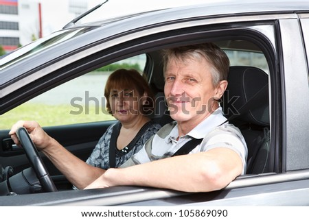 Mature happy Caucasian couple sitting in domestic car and smiling - stock photo